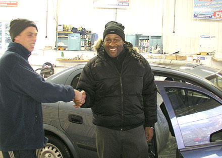 Ricky shaking hands with Sean when picking up his Vauxhall Astra